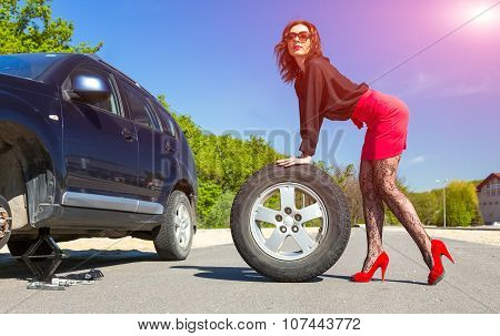 Sexy dressed female body holding car tire
