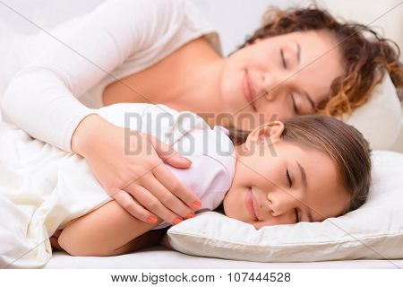 Delighted mother and daughter sleeping
