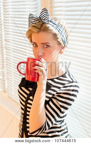 Pretty blond young woman drinking coffee or tea