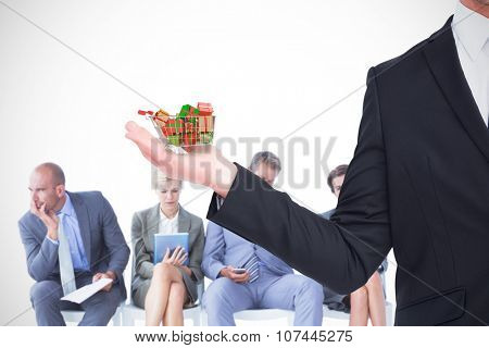 Businessman holding his hand out against trolley full of gifts