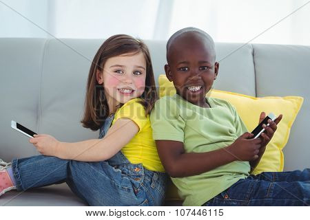 Smiling girl and boy using mobile phones on the couch