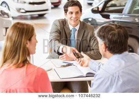 Smiling couple buying a new car at new car showroom
