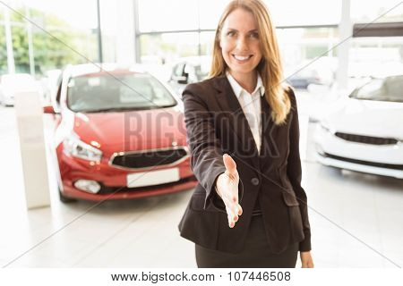 Smiling businesswoman reaching her hand at car showroom