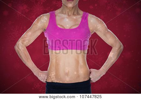 Female bodybuilder posing in pink sports bra and shorts mid section against snowflake pattern