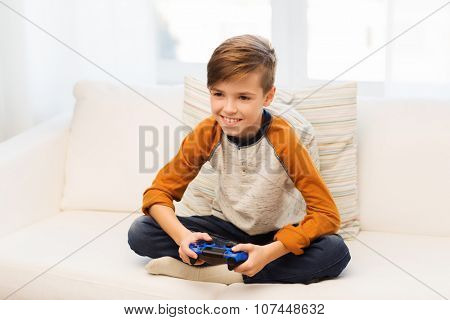 leisure, children, technology and people concept - smiling boy with joystick playing video game at home
