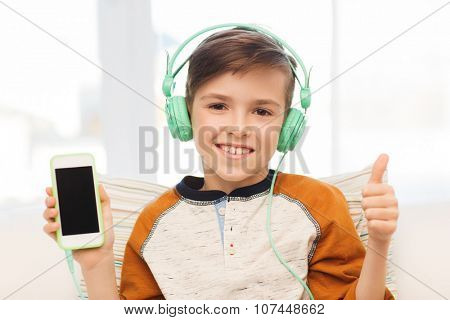 leisure, children, technology, gesture and people concept - smiling boy with smartphone and headphones listening to music and showing thumbs up at home
