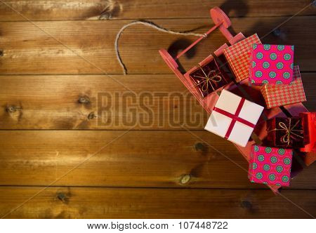 holidays, christmas, advertisement, new year and celebration concept - close up of many little gift boxes on red wooden sleigh on wooden board