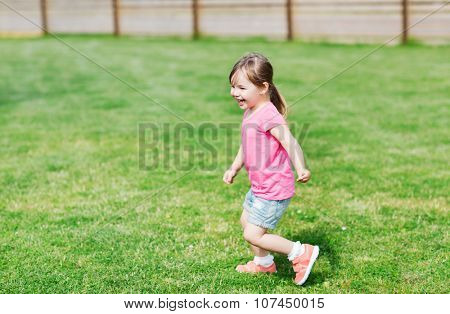 summer, childhood, leisure and people concept - happy little girl running on green summer field