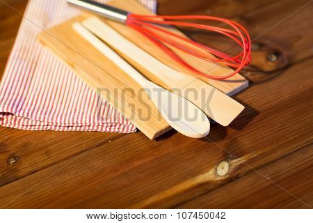 baking, cooking and home kitchen concept - close up of kitchenware and towel set on wooden board