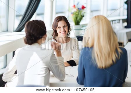 people, communication and lifestyle concept - happy women meeting and talking at restaurant