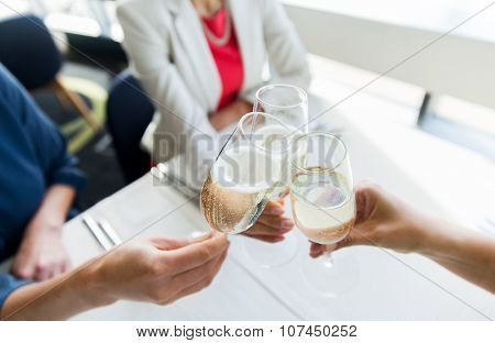 people, holidays, celebration and lifestyle concept - close up of women clinking champagne glasses at restaurant