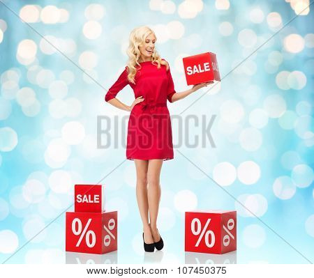 people, shopping, discount and holidays concept - smiling woman in red dress holding cardboard box with sale and percentage sign over blue holidays lights background