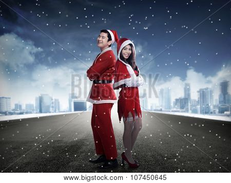 Happy Couple In Santa Claus Costume Standing On The Middle Of The Road