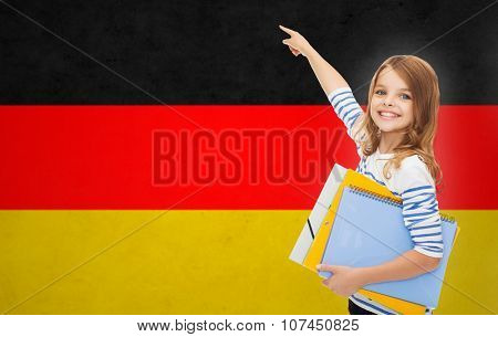 people, education, learning and school concept - happy student girl with folders pointing finger over german flag background