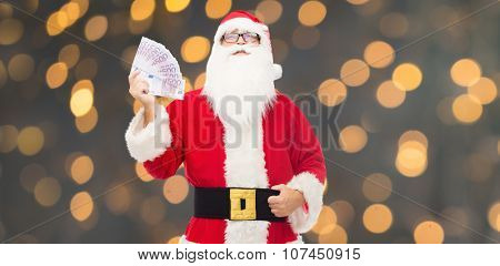 christmas, holidays, winning, currency and people concept - man in costume of santa claus with euro money over golden lights background