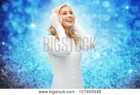 winter, fashion, christmas and people concept - smiling young woman in earmuffs and sweater over blue glitter or lights background