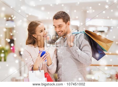 sale, consumerism, technology and people concept - happy young couple with shopping bags and smartphone talking in mall with snow effect