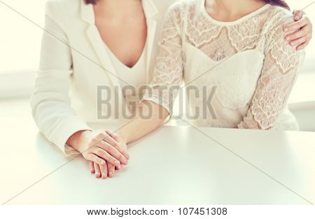 people, homosexuality, same-sex marriage and love concept - close up of happy married lesbian couple hugging