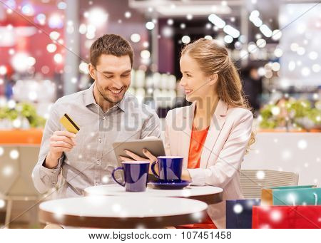 sale, shopping, consumerism, leisure and people concept - happy couple with tablet pc and credit card drinking coffee in mall with snow effect