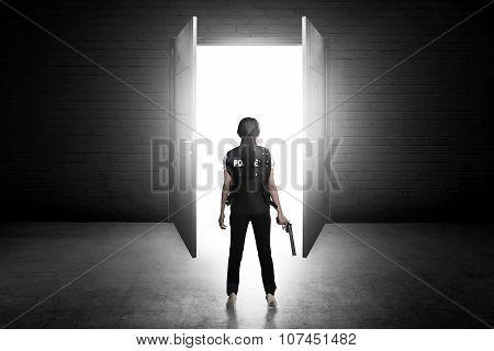 Police Woman Holding Gun Looking The Door