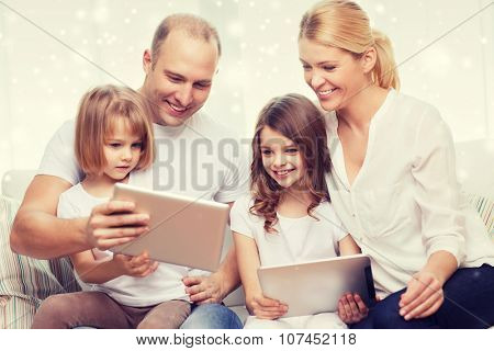 family, home, technology and people - smiling mother, father and little girls with tablet pc computers over snowflakes background