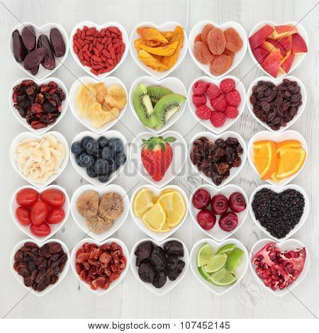 Healthy superfood fruit selection in heart shaped porcelain dishes over distressed wooden background, high in vitamins and antioxidants.