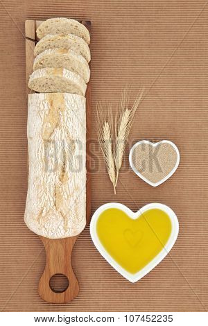 Ciabatta bread loaf on a wooden board with wheat sheaths and olive oil and yeast in heart shaped bowls on ridged brown paper background.