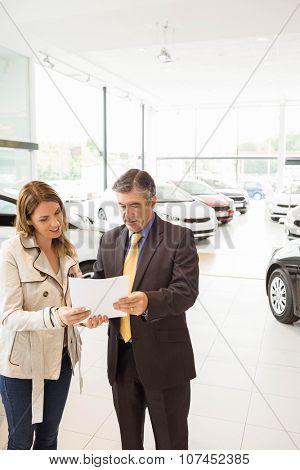Salesman explaining the contract to a client at new car showroom