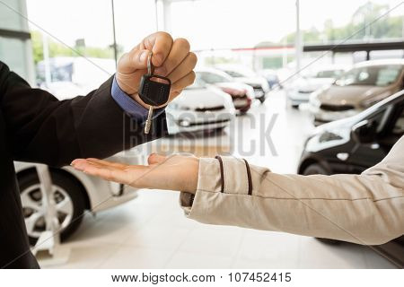Salesman offering car key to a customers at new car showroom