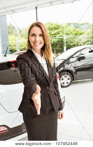Smiling saleswoman ready to shake hand at new car showroom
