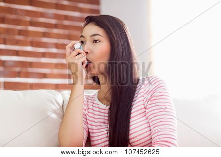 Asian woman using her inhaler on couch at home in the living room