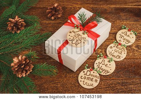 White Gift Box With Red Bow On Christmas Wooden Background