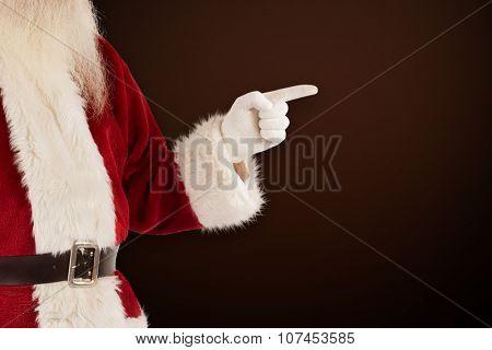 Santa Claus points at something against dark brown background