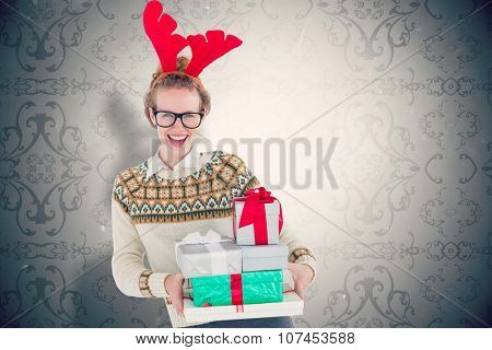 Happy geeky hipster holding presents against elegant patterned wallpaper in grey tones