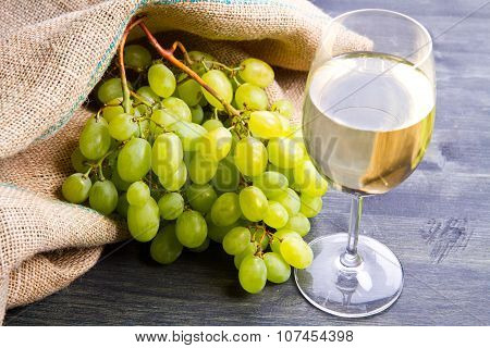 Bunch Green Grapes And Wine On Wooden Background