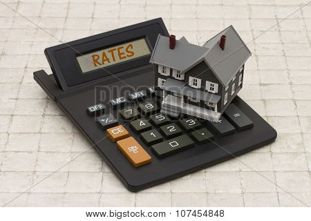 Home Mortgage Interest Rates, A Gray House And Calculator On Stone Background
