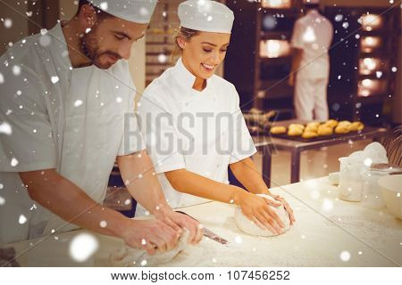 Snow against team of bakers kneading dough