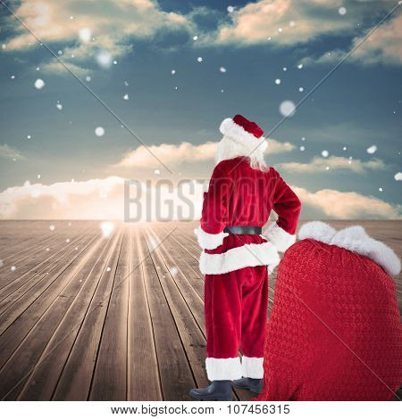 Happy santa with sack of gifts against wooden planks leading to blue sky