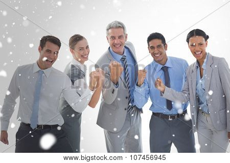 Portrait of successful business people clenching fists against snow
