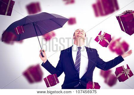 Businessman sheltering under black umbrella testing against red presents