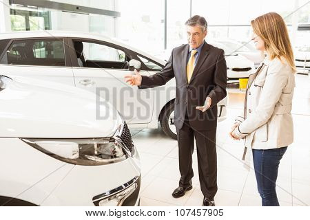 Salesman showing a car to a client at new car showroom