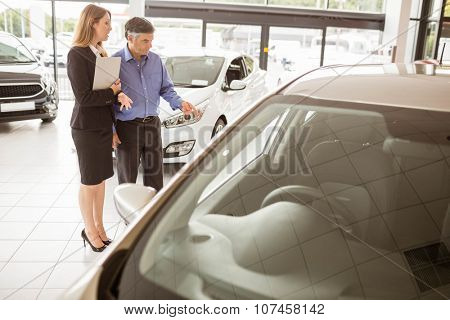 A man showing a car to the saleswoman at new car showroom