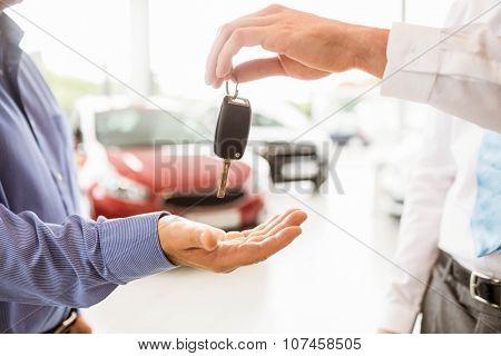 Businessman giving car key to a customer at new car showroom