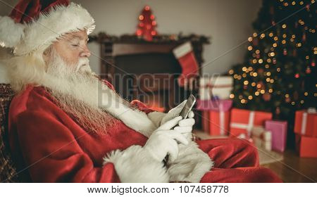 Concentrated santa using smartphone at christmas at home in the living room