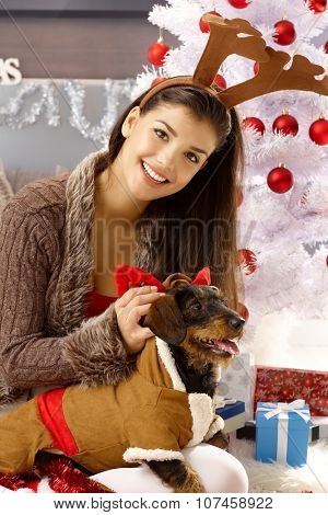Happy woman dressing up dog, smiling, looking at camera.