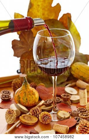 Glass of wine at vintage time among autumn decoration.