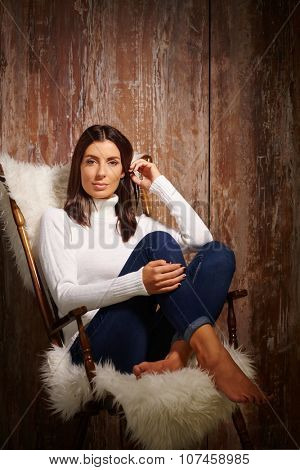 Attractive young woman sitting in armchair with pulled up legs in jeans and pullover, relaxing, looking at camera.