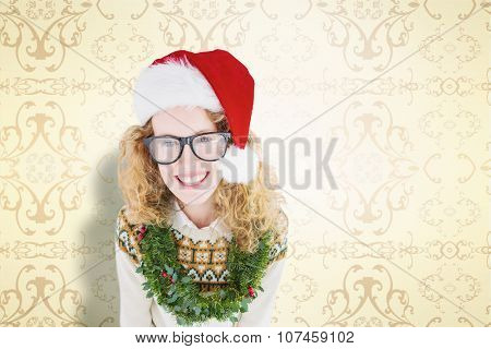 Geeky hipster smiling at camera against elegant patterned wallpaper in cream tones