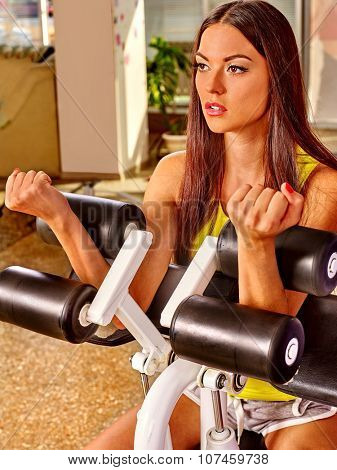 Girl with long hair workout on bicep curl machine in sport gym. Top view.