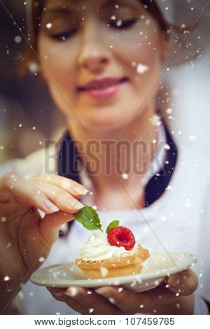 Snow against focused head chef putting mint leaf on little cake on plate
